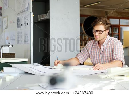 Young architect working on drawing table in architect studio.