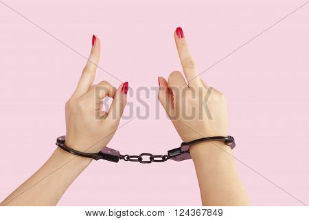 Beautiful female hands in black handcuffs showing the middle finger isolated on pink background. Submission trust and passion concept.