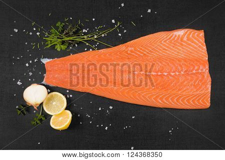 Fresh raw salmon background. Salmon steak lemon rosemary and parsley leaf and salt on black background flat lay.