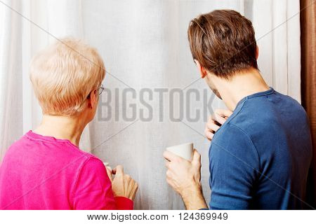 Mother and son standing next to the window, talking to each other and drinikin coffee or tea