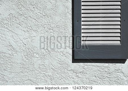 Slate Blue Shutter on Exterior Stucco Wall