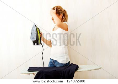 Young aghast woman standing behind ironing desk with iron in hand