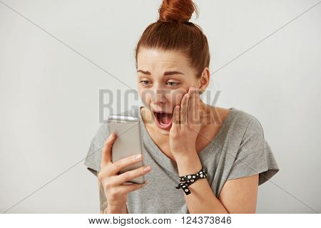 Closeup portrait smiling or laughing young freelancer woman looking at phone seeing good news or photos with nice emotion on her face isolated wall background. Human emotion reaction expression.