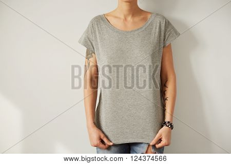 Girl Wearing Grey Blank T-shirt Standing On The Background Of A White Wall.