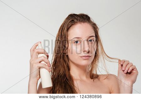 Beautiful woman spraying hairspray isolated on a white background
