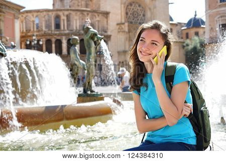 Young happy girl talking on smartphone smiling. Valencia Spain. Travel and tourism concept.