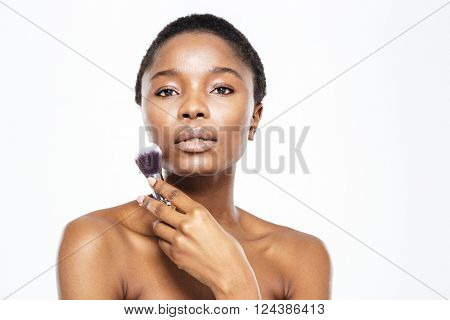 Beauty portrait of afro american woman holding makeup brush isolated on a white background