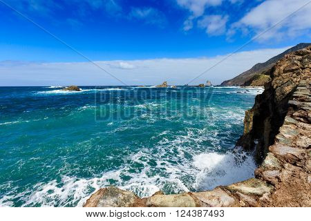 Summer seascape on tropical island Tenerife, Canary in Spain. Playa de Roque de Las Bodegas with giant rock and high waves.