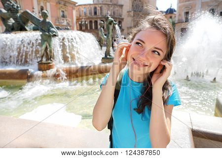 Happy Young girl wearing headphones listening to music traveling in Valencia Spain. Travel and tourism concept.