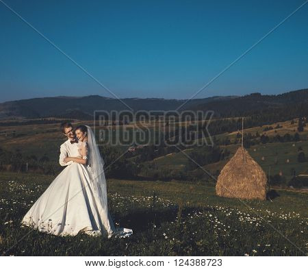 Beautiful wedding in the mountains, a young happy couple near the hayloft.