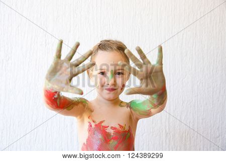 Little girl showing her hands covered in finger paint after painting a picture and her body with it. Playfulness creativity permissive parenting fun childhood concept selective sharpness.