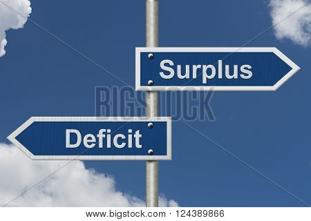 Difference between a Surplus and a Deficit Two Blue Road Sign with text Surplus and Deficit with sky background