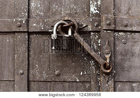 Steel padlock keeping the old door heck at the iron forged old door. Focus at the padlock and door heck. Textured metal rusty background