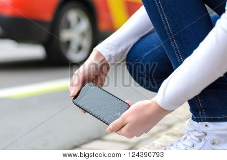 Young Woman Picking Up Her Shattered Mobile