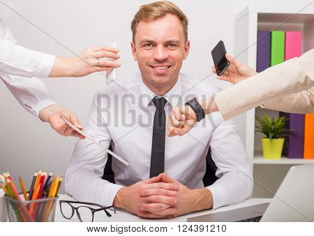 Happy man at the office having a lot of work