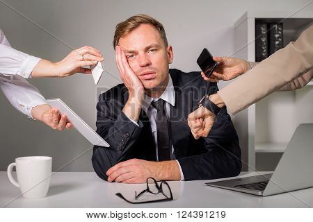 Tired man being overloaded at work with many tasks