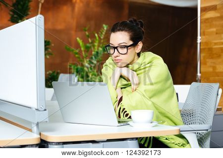 Beautiful thoughtful young woman coveted with coverlet using laptop and feeling cold on workplace