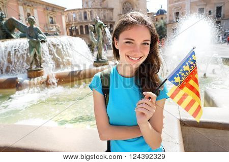 Happy young woman with flag of Valencian Community in front of Cathedral in Valencia Spain. Travel and tourism concept.