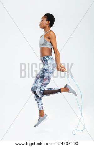 Sied view portrait of afro american woman jumping on skipping rope isolated on a white background