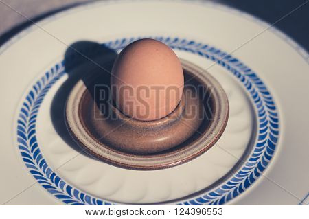 boiled egg in eggcup on beautiful porcelain plate - vintage style