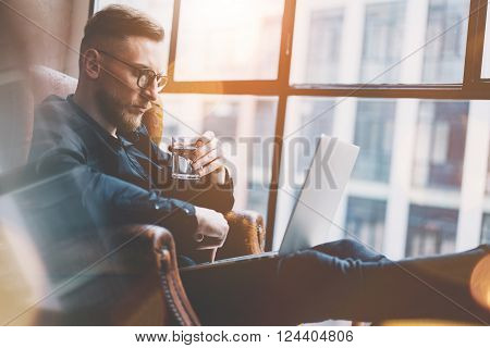 Bearded young businessman working on modern loft office. Man sitting in vintage chair. Using contemporary notebook, panoramic windows background.