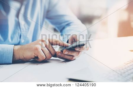 Office world, time brake. Businessman working at the wood table with new business project. Man touching screen modern mobile phone. Horizontal mockup.