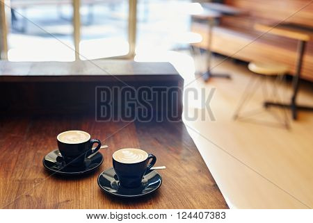 Two ceramic cups with saucers containing freshly made cappucinos, sitting on the wooden counter top of a coffee shop with light pouring in through the glass doors
