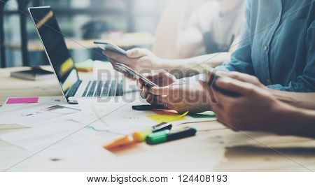 Team coworking process. Photo young business crew working with new startup project.Notebook on wood table. Using modern smartphones, typing message, analyze plans. Blurred background, film effect.