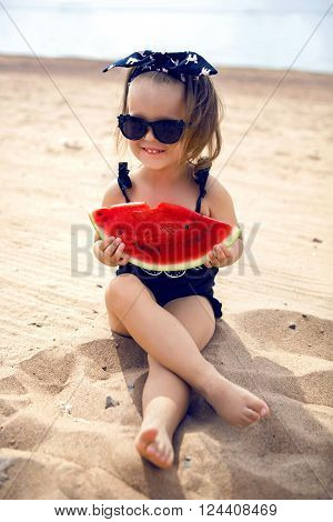 a little girl stands on the shore of the beach in a black bathing suit and black glasses eating juicy watermelon sitting