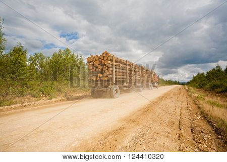 Trailer truck loaded with wooden beams traveling on a dirt road.