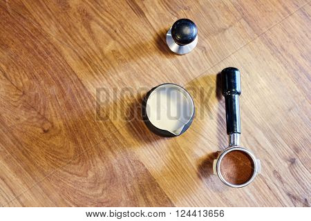 Overhead shot of some espresso machine accessories lying on a wooden surface: a metal jug with steamed milk in it, a new portafilter neatly packed with freshly ground coffee, and a metal tamper