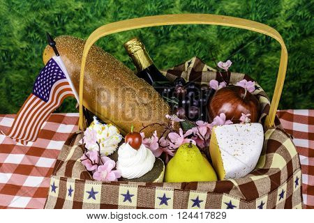 picnic basket with fruit cheese bread cupcakes champagne and american flag on green background