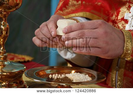 Hands of priest consecrates bread during orthodox liturgy ceremony poster