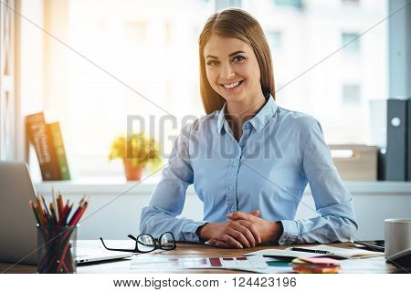 Toothy smile from real expertise. Cheerful young beautiful woman looking at camera with smile while sitting at her working place