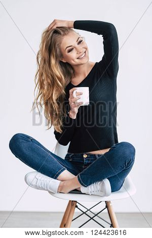 Cheerful beauty. Beautiful young woman holding coffee cup and looking away with smile while sitting on chair in lotus position against white background