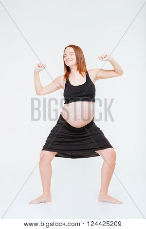 Full length portrait of a happy redhead woman posing isolated on a white background