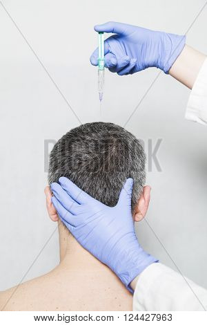 Doctor aesthetician makes hyaluronic acid beauty injections in the forehead of male patient in a medical cap and white t-shirt poster