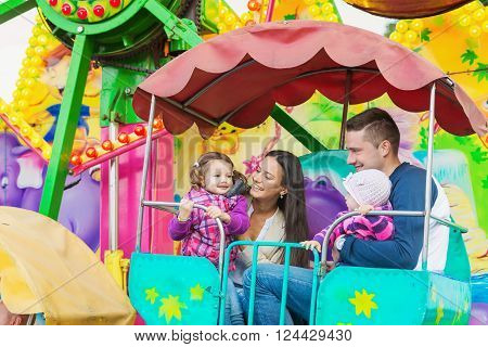 Cute little girls with their mother and father enjoying ride at fun fair, young family, amusement park