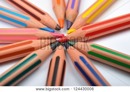 Close Up Picture Of Colored Pencil Crayons With Stripes Arranged In Circle On White Background. Asso