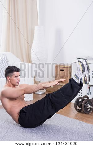 Strong young man doing crunches on floor