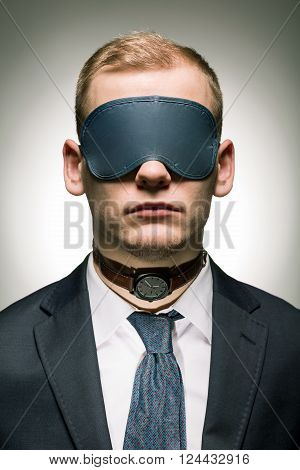 Young employer of corporation in suit with band on eyes and watch on his neck