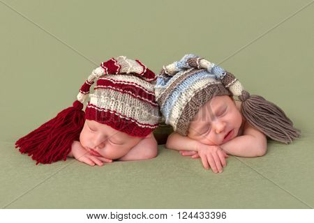 3 weeks old identical twin girls sleeping on a green backdrop