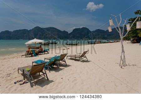 PHI PHI DON, THAILAND - MARCH 2: Tropical island with resorts and sandy beach with lounge chairs on March 2, 2015. Tropical Ko Phi Phi National Park covers about 39000 hectares