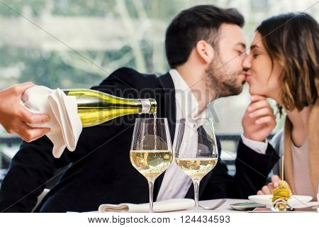 Close up of wine steward pouring white wine in glass with out of focus kissing couple in background.