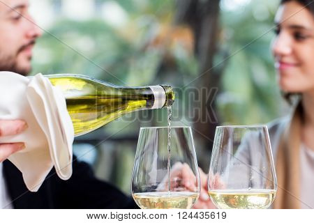 Close up of waiter pouring white wine in glass with couple in background.