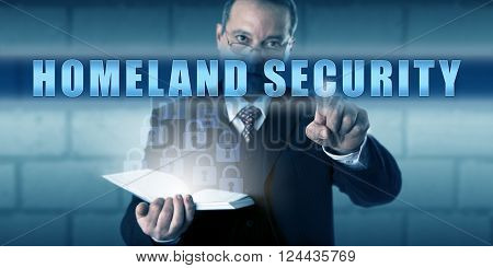 Governmental protection professional is pushing HOMELAND SECURITY on a virtual touch screen. Business metaphor and security industry concept for emergency preparedness and threat prevention.