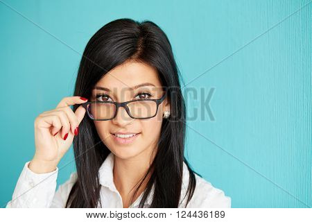Portrait Of Woman In Glasses Standing Over Blue Background