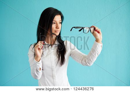 Pensive Woman With Glasses Standing Before Blue Background