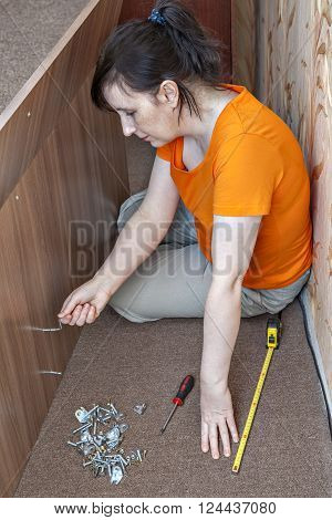 Assembling of furniture at home woman housewife collects double bed using the hand tool hex wrench allen key.