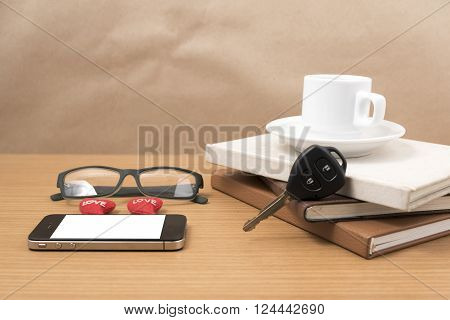 office desk : coffee and phone with car key eyeglasses stack of book heart on wood background